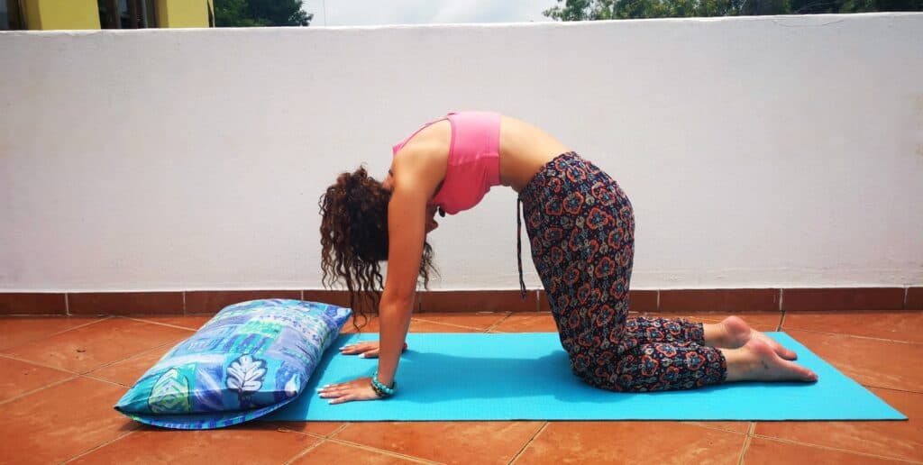 Yoga teacher doing Cat-Cow on balcony to show users what the posture must look like.