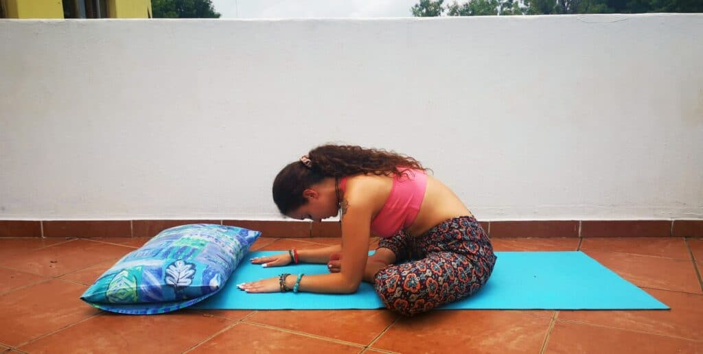 Yoga teacher doing Butterfly Pose on balcony to show users what the posture must look like.