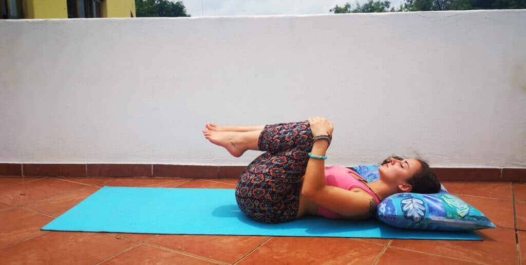 Yoga teacher doing Knees-to-Chest Pose on balcony to show users what the posture must look like.