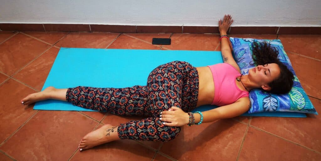 Yoga teacher doing Reclined Spinal Twist on balcony to show users what the posture must look like.