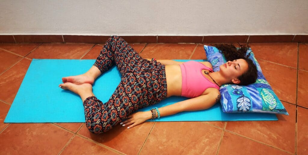 Yoga teacher doing Reclined Butterfly Pose on balcony to show users what the posture must look like.