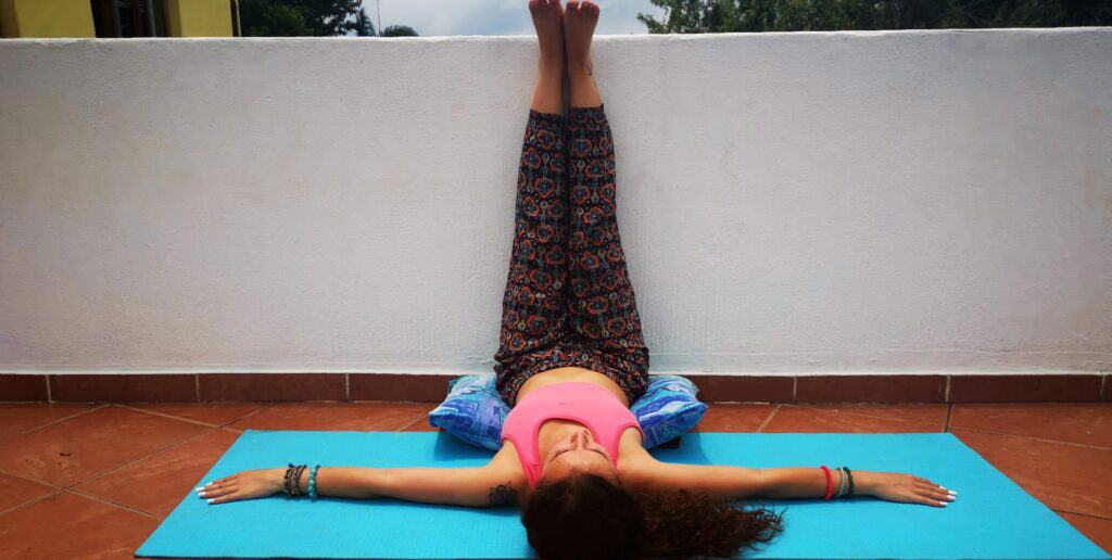 Yoga teacher doing Inverted Leg Pose on balcony to show users what the posture must look like.